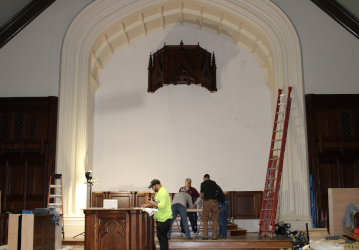 Workers stand under the first piece of the reredos currently being installed in Our Mother of Perpetual Help Chapel.
