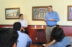 Mark Kretschmer ('99) speaks with students in the campus coffee shop.