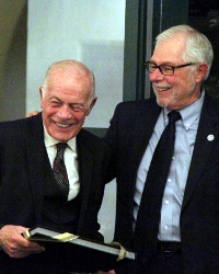 President McLean (right) presents Mr. DeLuca with a photo album chronicling his career at Thomas Aquinas College