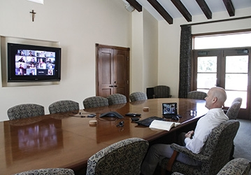 Tutor Brian Dragoo leads a class from the St. Thomas Hall conference room on the California campus
