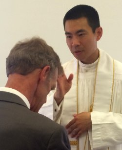Fr. Jacob offers a blessing to Director of Gift Planning Tom Susanka
