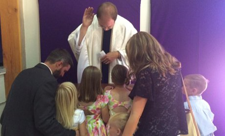 Fr. Mayer blesses the Minkel family