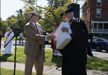 Donald G. Glascoff, Jr., presents President Michael F. McLean with a 400-year old edition of the Summa Theologiae on New England Convocation Day