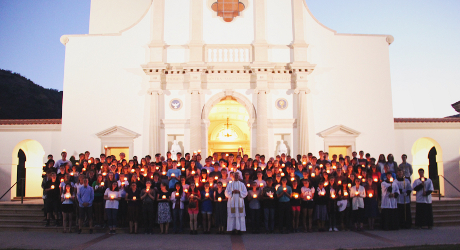 Students holding candles in the plaza of Our Lady of the Most Holy Trinity Chapel