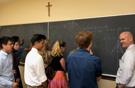 Students and a tutor demonstrate Euclidean propositions on the chalkboard