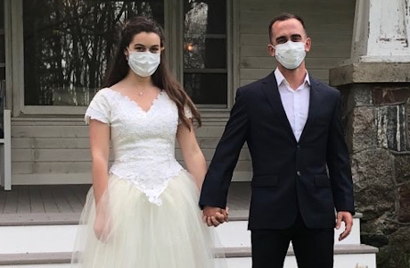 Mr. and Mrs. Nazeck in wedding clothes and medical masks