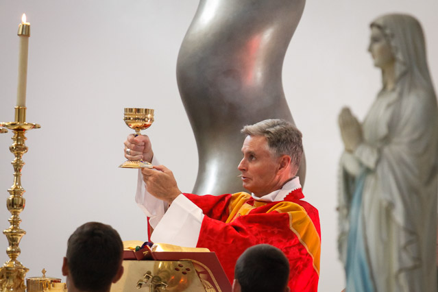 Bishop Daly elevates the chalice.