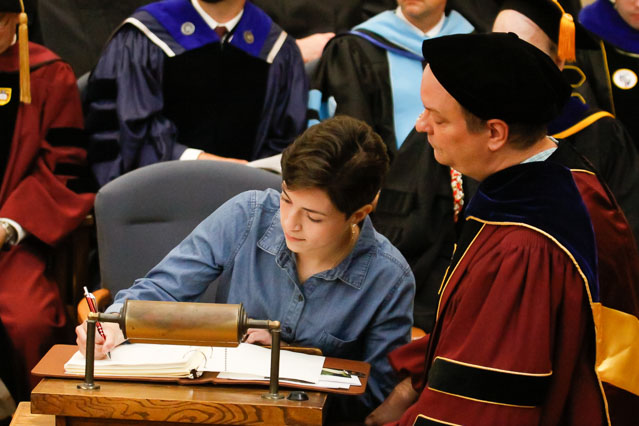 Registrar and Tutor Dr. Phillip Wodzinski looks on as members of the Class of 2022 sign their names in the registry
