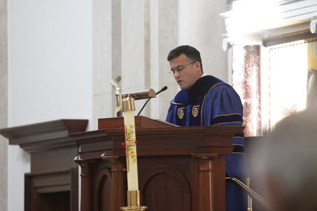 Tutor Dr. Marco Emerson offers the prayers of the faithful.