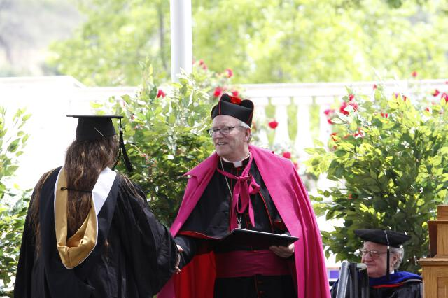 Bishop Barron distributes the diplomas.