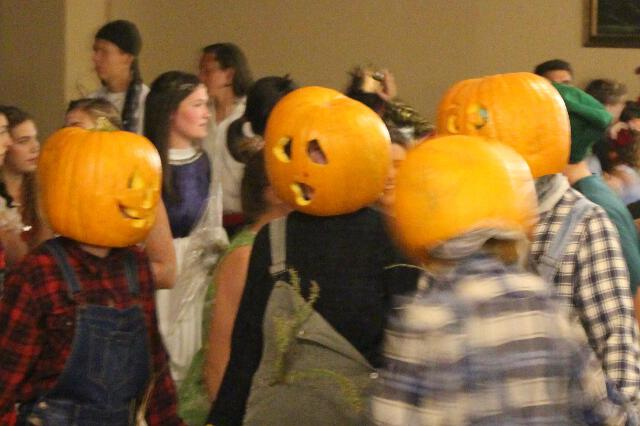 Four students wearing pumpkin heads
