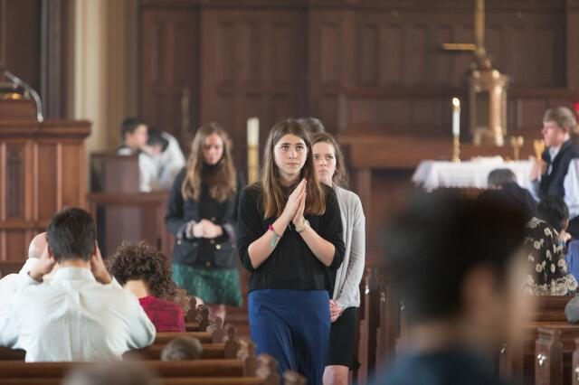 Worshipers return to their pews after receiving Holy Communion.