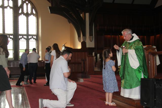 Rev. Charles Di Mascola, former pastor of Our Lady of Czestochowa Parish in Turners Falls, Massachusetts, distributes Holy Communion.