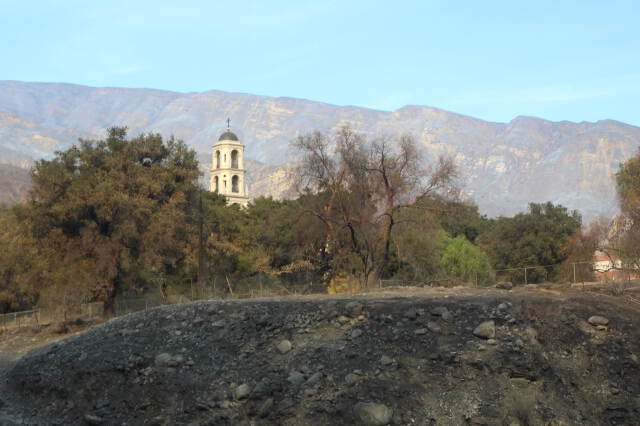 From Highway 150, Our Lady of the Most Holy Trinity Chapel with charred brush in the foreground