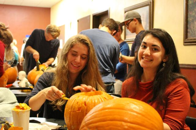 Students carve pumpkins in the Dumb Ox Cafe