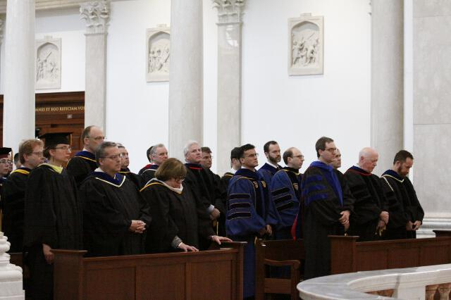 Faculty in the chapel, dressed in academic regalia