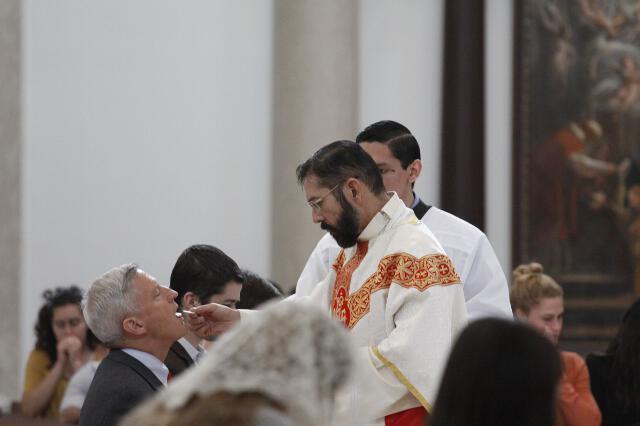 Bishop Flores distributes Holy Communion