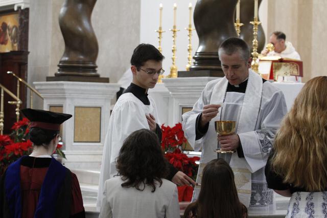 Chaplain Rev. Robert Marczewski distributes Holy Communion
