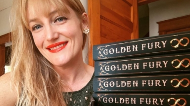 "Samantha Cohoe next to a stack of copies of ""A Golden Fury"""